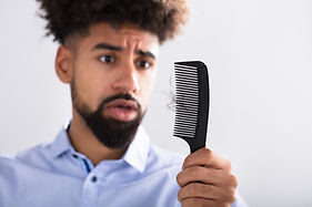 Young Man Holding Comb Looking At Hair L