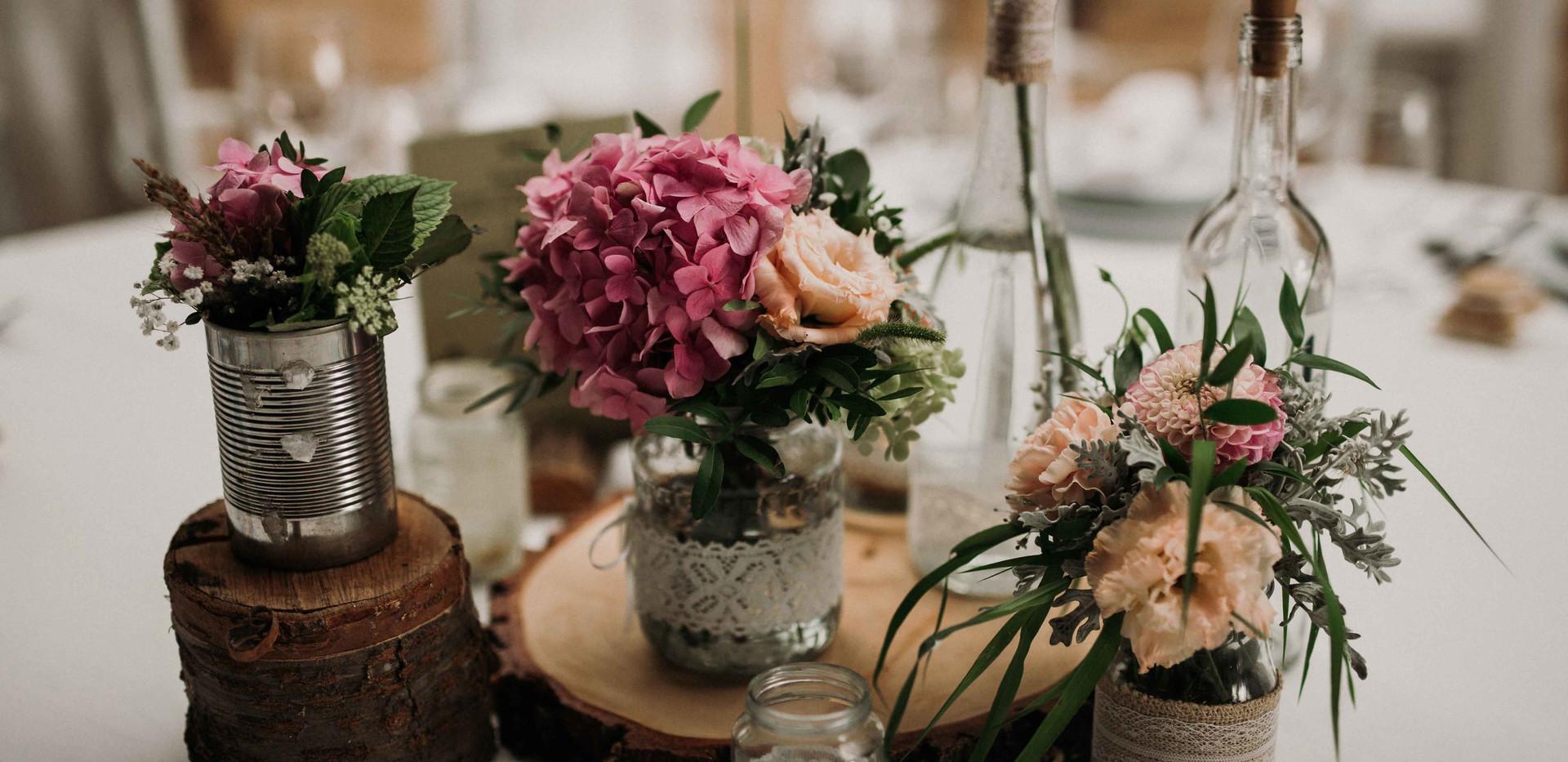 Asztali dekoráció, fakorongok, hasábok, csipkés üvegek élővirágokkal, rusztikus összeállításban