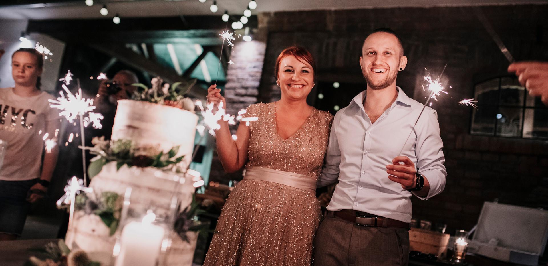 Az esküvői torta, kézzel díszítve mezei kiegészítőkkel és pozsgásokkal, csillagszóróval