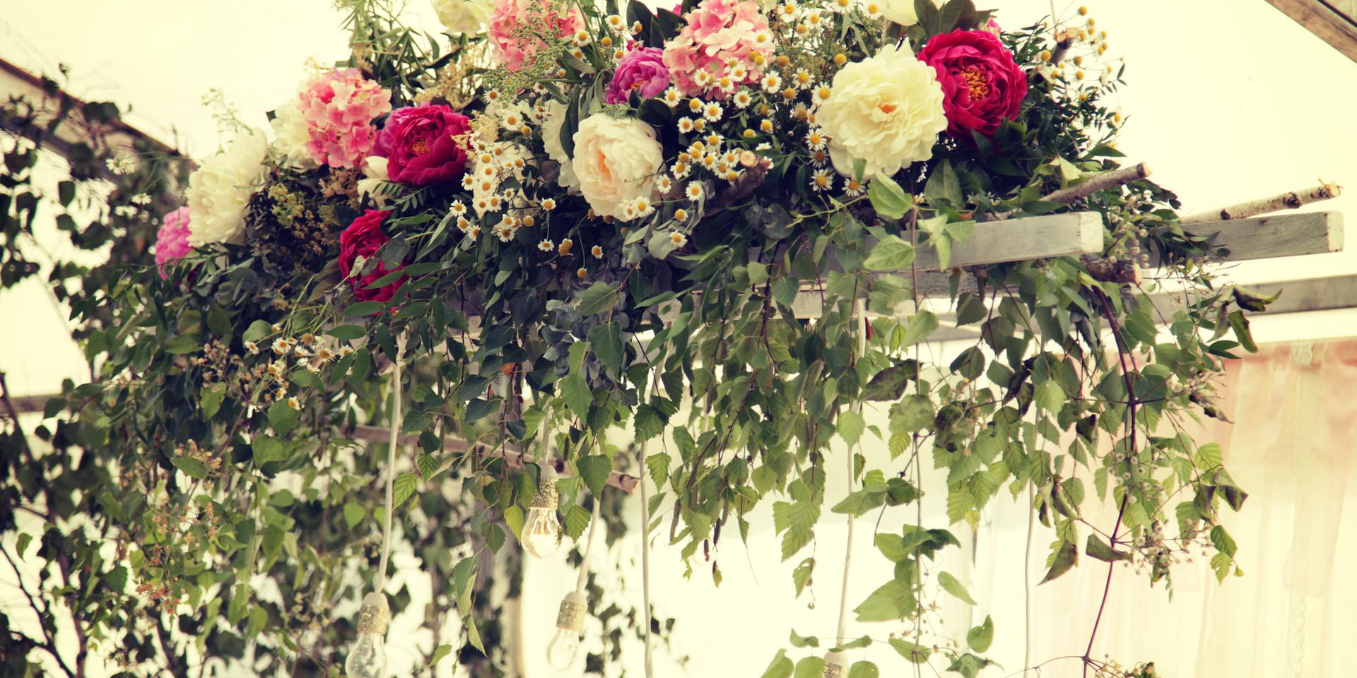 Esküvői virágdísz a főasztal felett