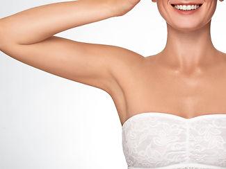 Zgrabne ramię kobiety i część twarzy z uśmiechem