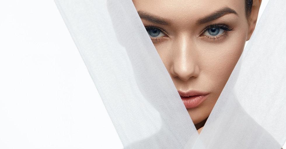 Częściowo osłonięta twarz młodej kobiety z gładką skórą i niebieskimi oczami