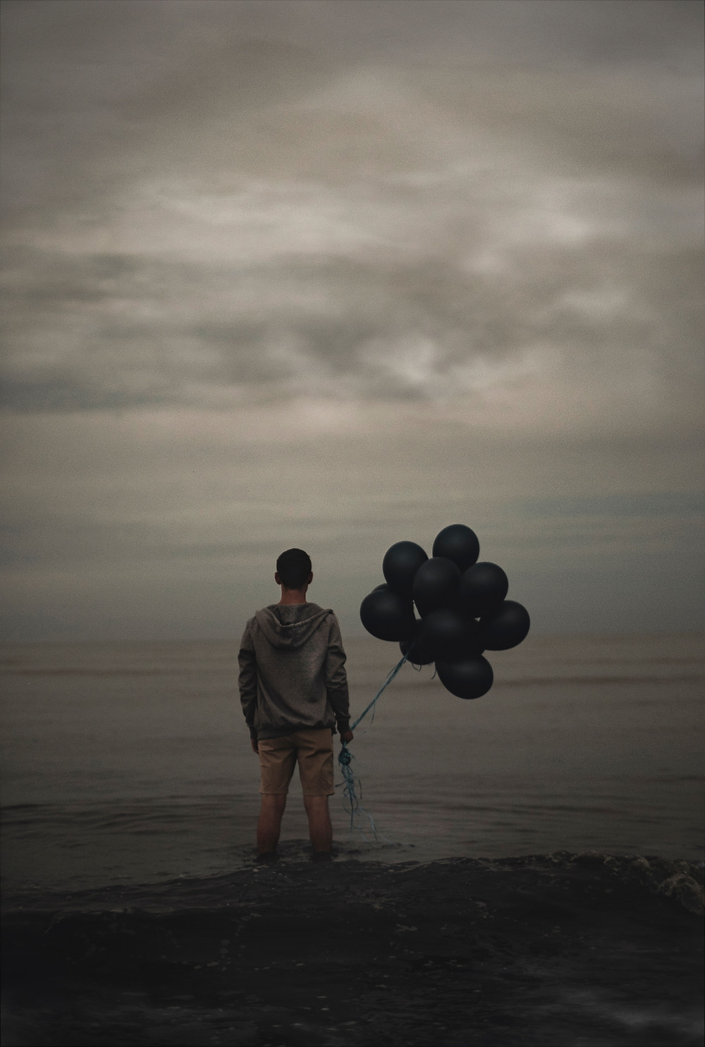 Photo of young man holding black balloons overlooking the ocean
