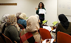 A volunteer using Lissan NGO's special book to teach Arab women Hebrew