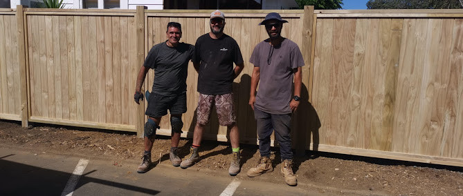 Team of builders in front of finished fencing project