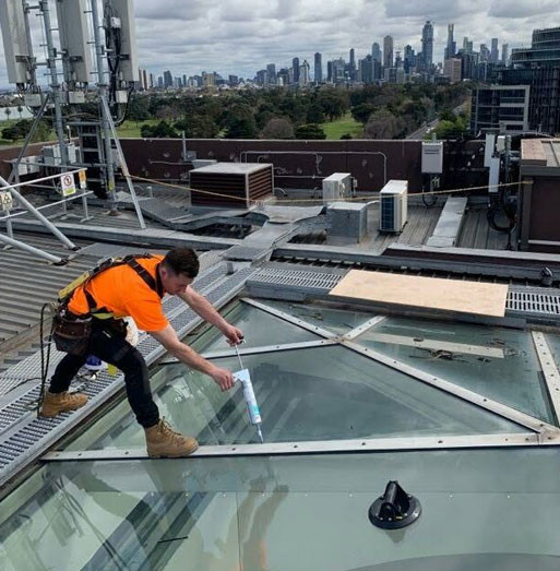 tradie installing glass on commercial building