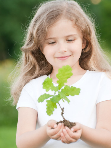 Little girl and young plant of a oak.jpg