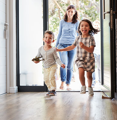 a mother and two happy children walking in the door