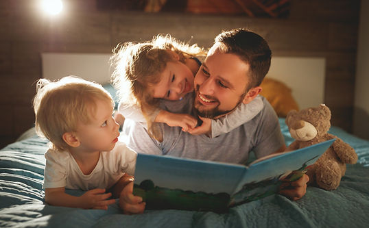 a happy father reads to his two young children