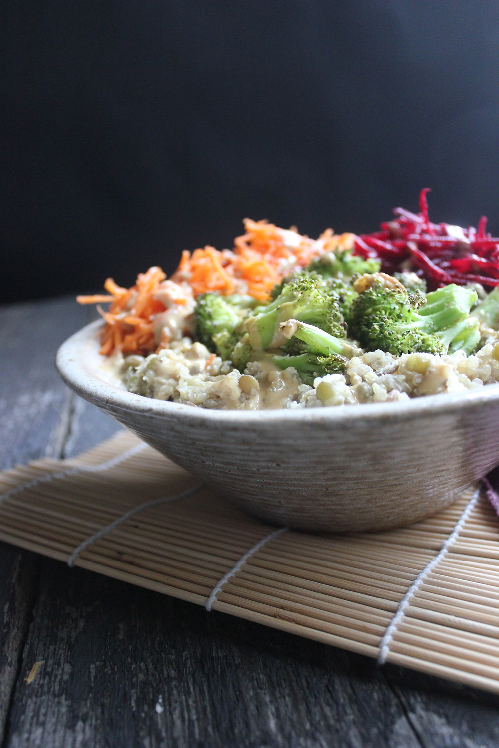 A simple, hearty and comforting nourish bowl made with quinoa, mung beans, lentils and topped with shredded beets, carrots, roasted broccoli, and homemade miso gravy.