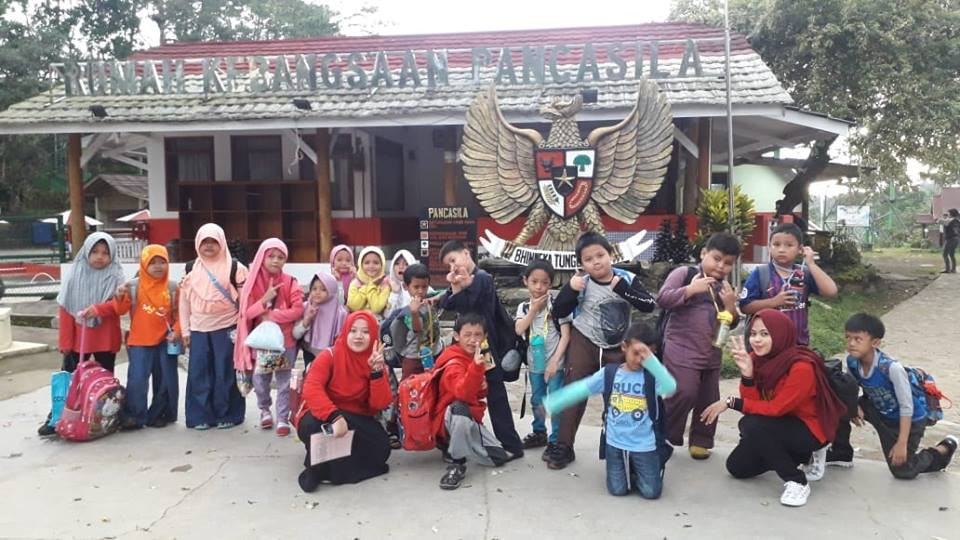 keceriaan anak berpose di depan rumah kebangsaan pancasila