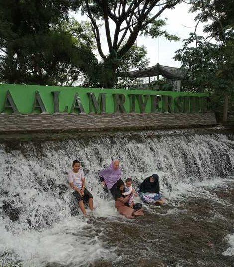 bermain di air terjun bersama keluarga