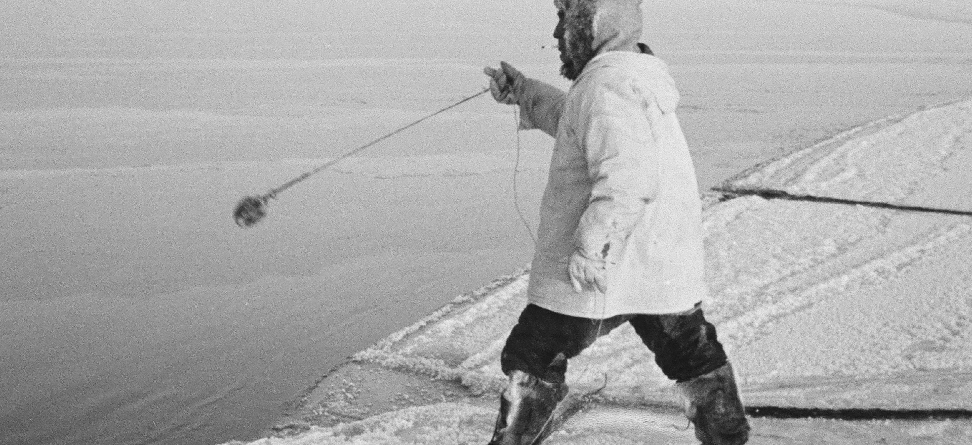 Anaqqaq Ekak tossing a manaq (wooden float with metal hooks) to retrieve a seal shot in open water. He's standing on his unaaq to distribute his weight on the thin ice.