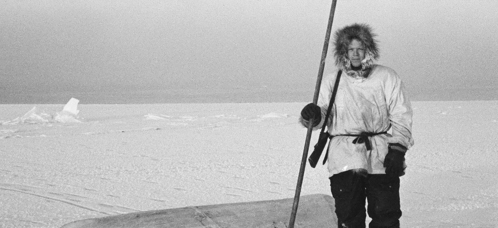Richard Nelson on young ice with open water in the background. Rifle over his shoulder, he holds an unaaq used to test ice thickness. The umiaqaluraq is used to retrieve seals. (Wainwright, Alaska 1964)