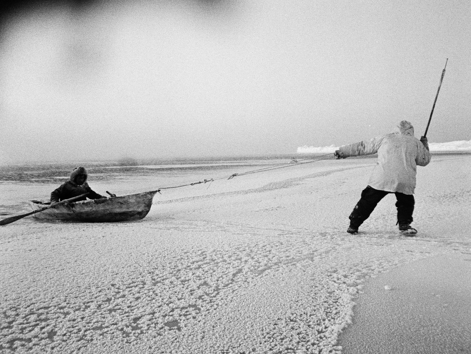 A hunter pulling his companion over thin ice. The umiaqalrulaq (skin boat) was used to retrieve a seal shot in open water.