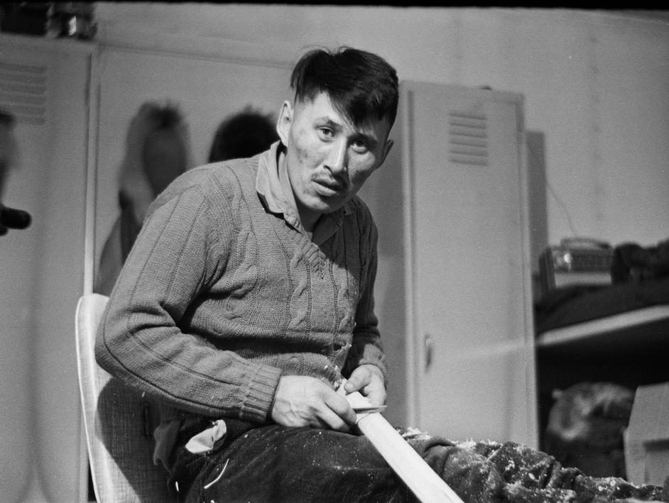 Tagruk Bodfish carves a kayak paddle in Richard's Wainwright home (1964).