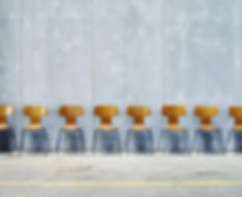 row-of-empty-chairs-against-wall-henrik-