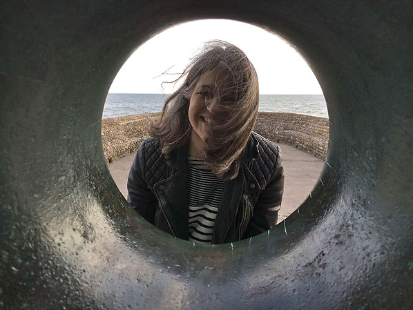 Photograph of Laura looking through a sculpture