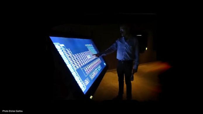 Sallim_Edde devant l'écran interactif des éléments.