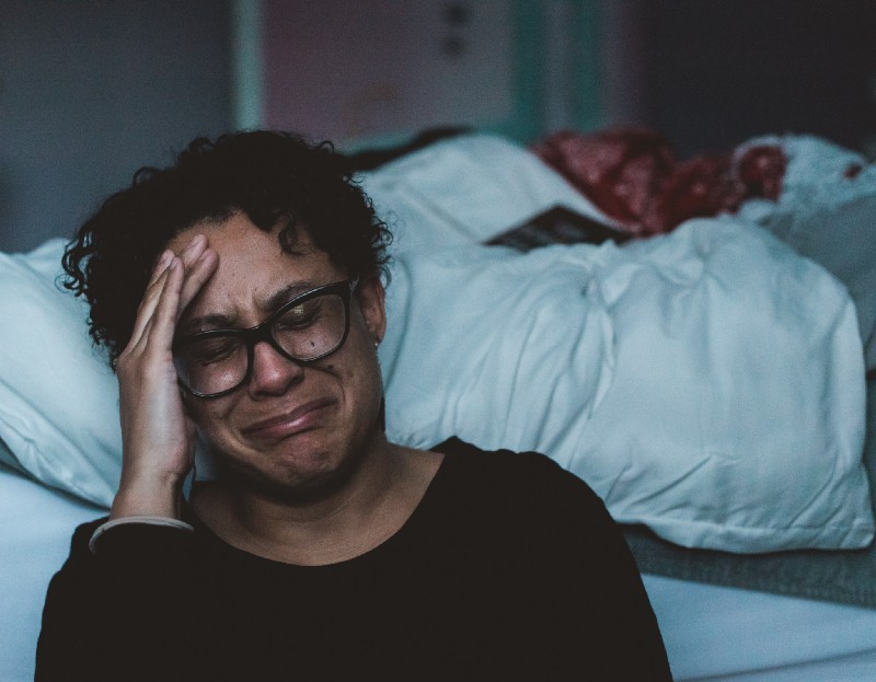 black female wearing dark rimmed spectacles seated on the floor next to her bed crying
