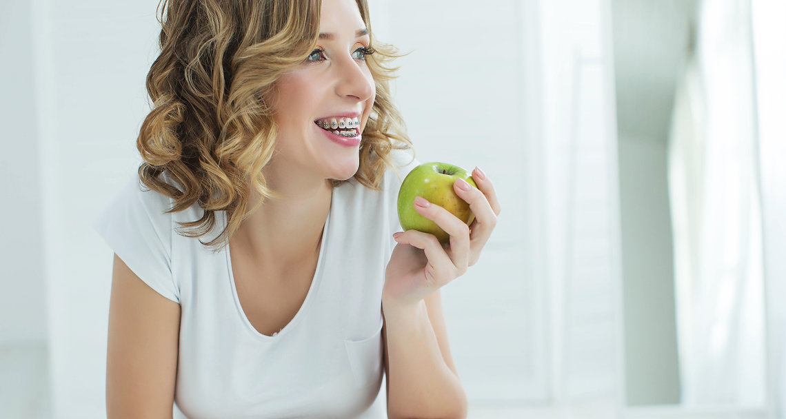 Young woman in braces with apple