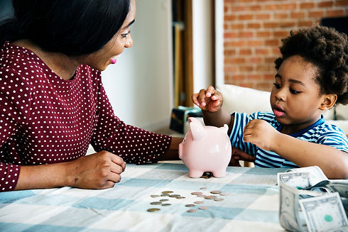 Mom and son saving money to piggy bank.j