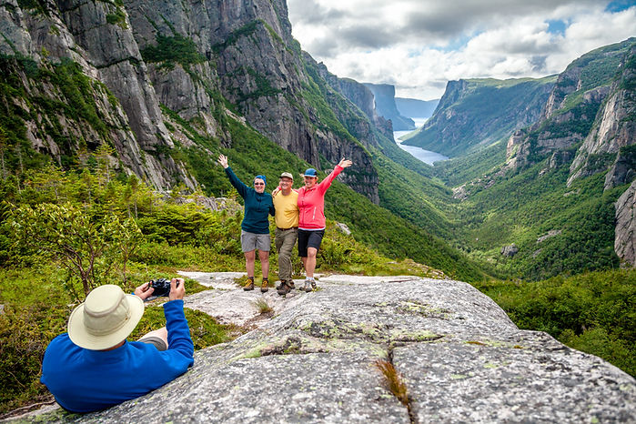 Hikers pose for a photo on top of Western Brook Pond Fjord in Gros Morne.
