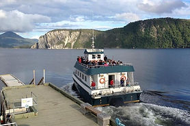 A passenger boat sails away from the dock towards beautiful mountains and fjords.