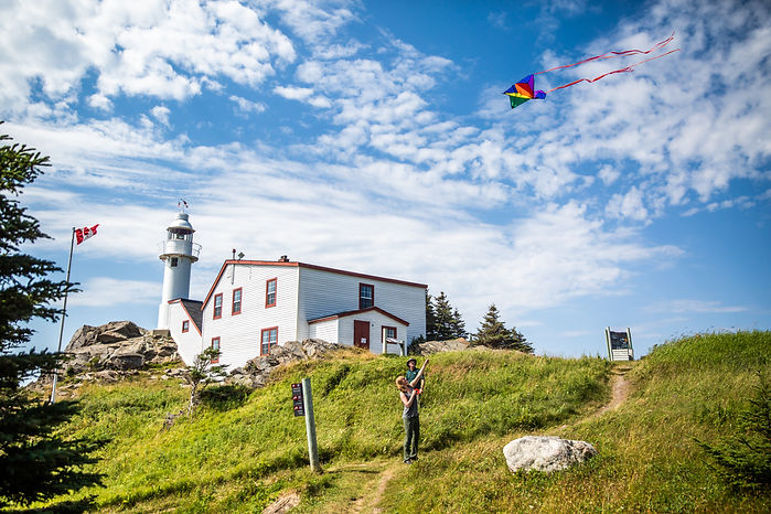 Two people fly a kite near the historic Lobster Cove Head Lighthouse in Gros Morne.