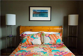 A room with a colourful quilt and pillows against a wooden bed frame.