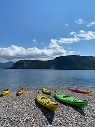 Kayaks sit on a pebbly beach in Bonne Bay, Newfoundland.