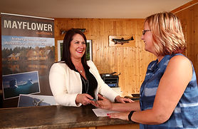 A receptionist greats a guest checking into a rustic inn.