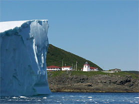 An iceberg floats next to a lighthouse and cafe in St. Anthony, Newfoundland.