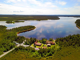 Aerial view of a lodge on the shores of a lake surrounded by boreal forest.