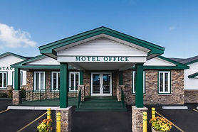 """A bright, crisp image of the entryway into Shallow Bay Motel. The building is brick with an overhand and two green pillars, deep green steps, and a ramp. The words """"Motel Office"""" are on the overhang."""