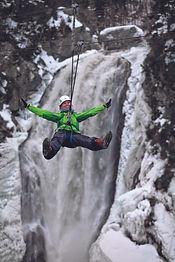Woman in green coat ziplines across Steady Brook waterfall.