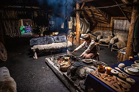 A guide dressed in traditonal Viking clothing prepares a meal in a reconstructed sod hut.