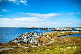 A man walks along a coastal trail in the town of Isle aux Morts, Newfoundland.