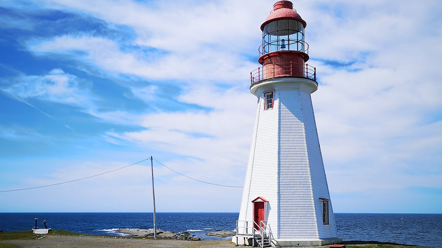 The white Point Riche Lighthouse in Port au Choix, Newfoundland, stands against the a cloudy sky.