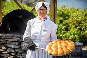 A woman in traditional clothing holds freshly baked buns in front of a French Bread Oven.