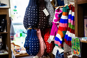 Colourful home-knit mittens and socks hang neatly on display.