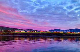A strip of colourful cabins in orange, yellow, red, and blue is cushioned between a pink sunset sky and the reflection in the water.