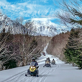 Snowmobilers ride a groomed trail among the trees and mountains.