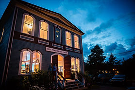 The Heritage Theatre in Woody Point with the windows lit up at night.