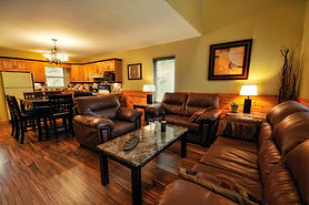 A cozy condo room with brown leather couches and wine on the coffee table.