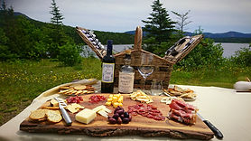 A charcuterie board, wine, and picnic basket in a outdoor setting.