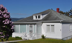 The outside of a house named Aunt Dorothy's Place. The siding is white and mint with a charming step up to the front door.