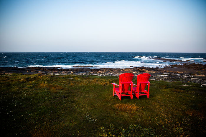 Two red adirondack chairs sit on the grass facing the ocean as waves break on the rocky shore.