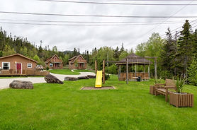 The property at Middle Brook Cottages is full of well-maintained green grass. A slide and swingset are in front of a wodden gazebo and two wood cottages are in the back.