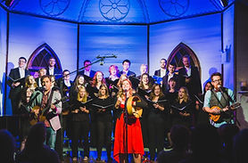 A choir dressed in black stands in St. Pat's church. In front of them, the lead singer of the Once sings and plays bodhran in a red dress.
